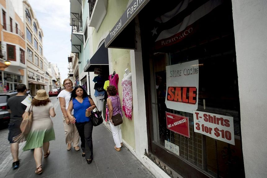 People walk past a closed store in San Juan, Puerto Rico, on July 31, 2015.
