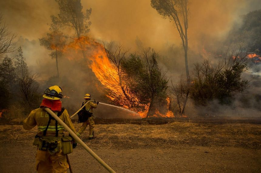 Firefighters douse a backfire while battling the Rocky fire near Clearlake, California.