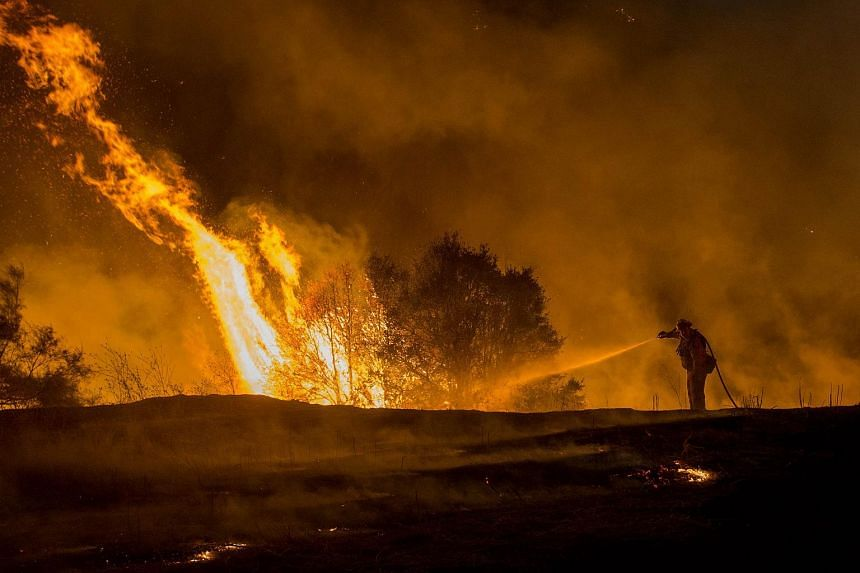 Firefighter Joe Darr douses flames of the Rocky fire along Highway 20 near Clearlake, California.