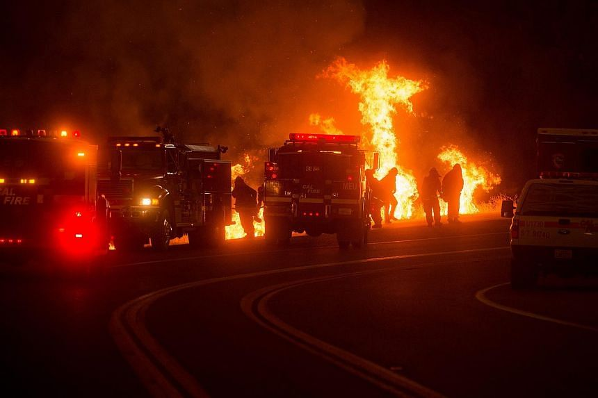 Flames from a backfire rise from a canyon as firefighters battle the Rocky fire near Clearlake, California.
