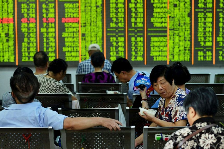 Investors have lunch in front of an electronic board showing stock information at a brokerage house in Hangzhou, Zhejiang province.