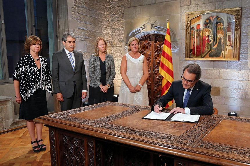 Catalan regional president Artur Mas (left) signing a decree at the Generalitat palace in Barcelona, calling early parliamentary elections.