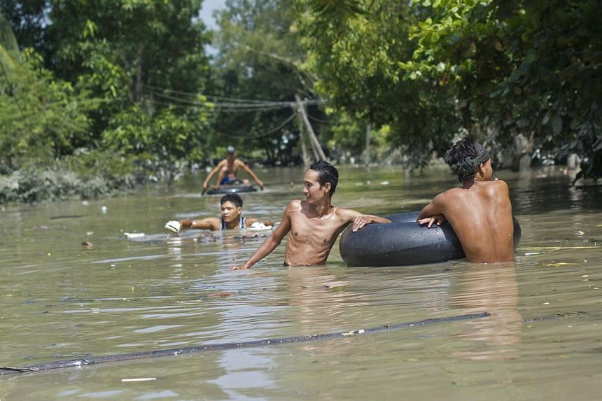 Flood-affected residents commute through floodwaters in Kalay, upper Myanmar's Sagaing region on August 3, 2015.
