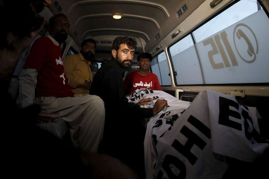 Abdul Majeed, brother of Shafqat Hussain who was convicted of killing a child in 2004, sits in an ambulance beside the body of Safqat after his execution on Aug 4, 2015.