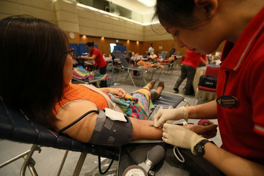 Staff and members of the public donating blood during SPH Red Apple Day.