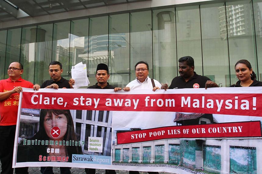 Protesters hold a banner while demonstrating against Sarawak Report founder and editor Clare Rewcastle-Brown on July 25, 2015.