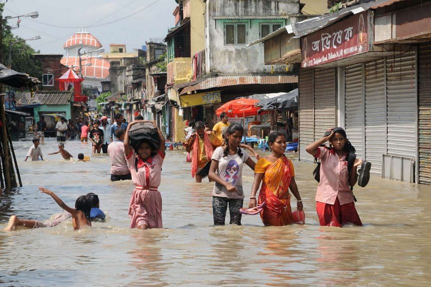 Indian women and children walk on a flooded street in Kolkata on Aug 3, 2015.