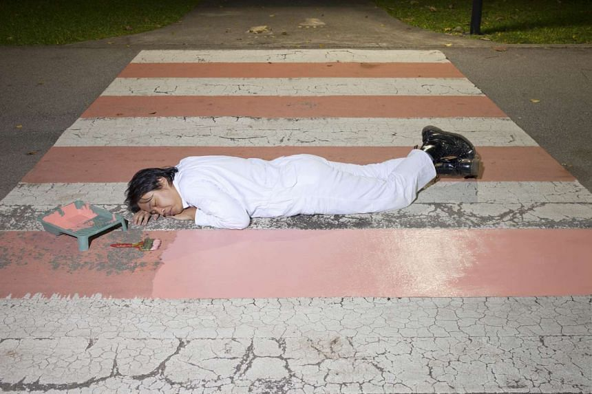 """Geraldine Kang's photographs, titled Under The Guise Of Surface in the Singapore Survey, include this one (above) of a worker painting weather-worn public structures. The work """"toes the line between artistic, maintenance and transgressive gesture"""