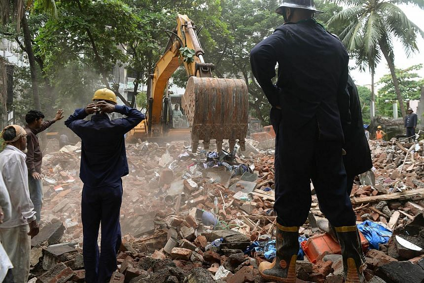 Rescue workers use an excavator to clear debris while searching for survivors at the site of a residential building collapse in Thane, near Mumbai, on Aug 4, 2015.