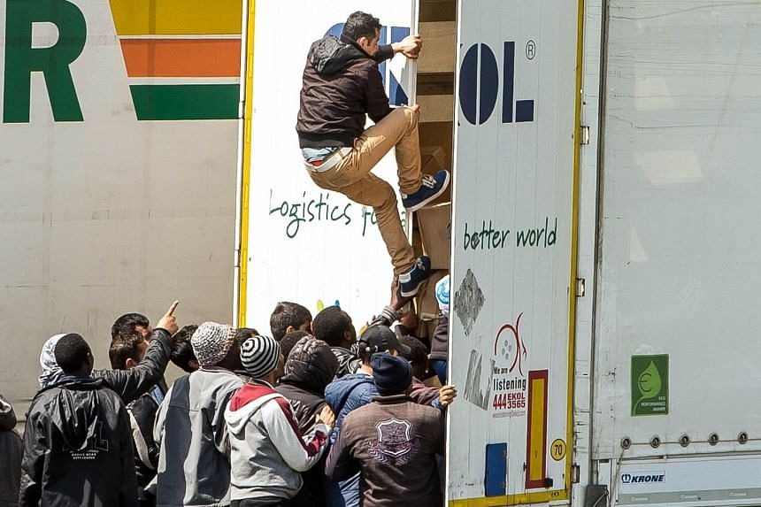 "Migrants climbing into the back of a lorry on a highway leading to the Eurotunnel, which connects France to Britain. Britain's reputation as a ""soft spot"" for migrants remains undiminished."