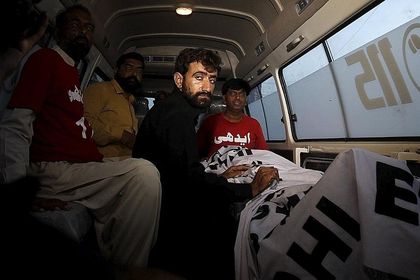 Mr Abdul Majeed, brother of Shafqat Hussain (right) who was convicted of killing a child in 2004, sitting in an ambulance beside Hussain's body after his execution in Karachi yesterday. Hussain's family and lawyers say that he had been under 18 at th