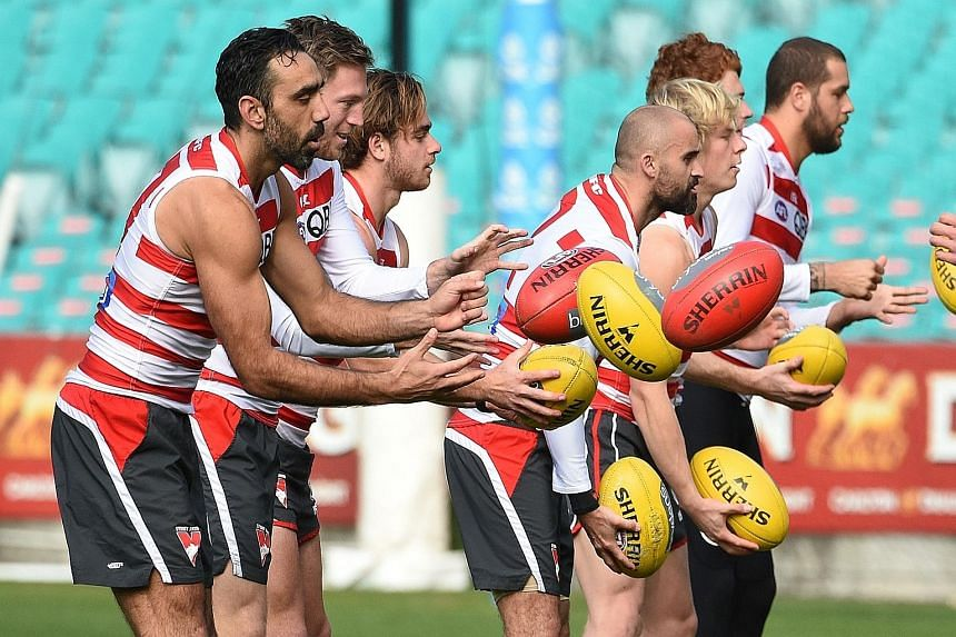 """Australian Rules star Adam Goodes (left) at training with Sydney Swans team-mates yesterday. Goodes - an indigenous player and the target of recent racial vilification - said he felt """"very loved"""" after widespread support."""