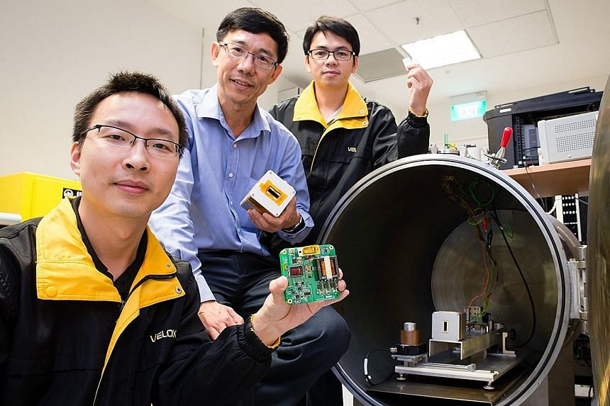 NTU's Associate Professor Low Kay Soon (centre) with his researchers on the project. The university worked with Japan's Kyushu Institute of Technology on a nanosatellite which will be delivered to the ISS for launch next year.