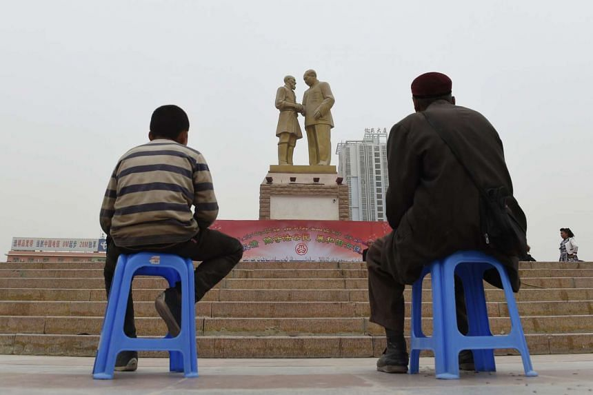 An Uighur man and boy watching a performance under a statue of late communist leader Mao Zedong meeting with an Uighur in Xinjiang.