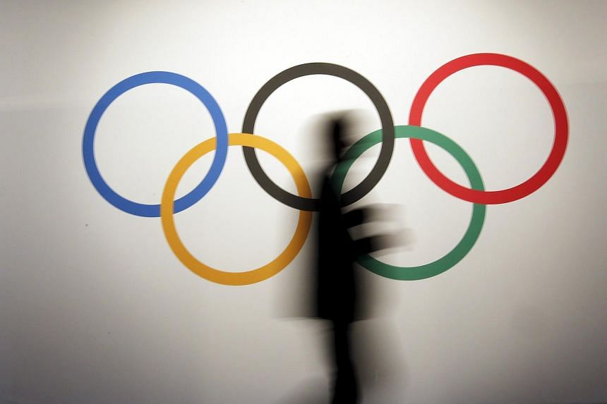 A man walks past the Olympic rings.