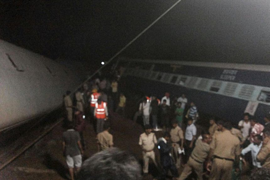 Police and members of the rescue operation standing at the site of a train derailment near Harda, Madhya Pradesh, in this handout provided by ANI.