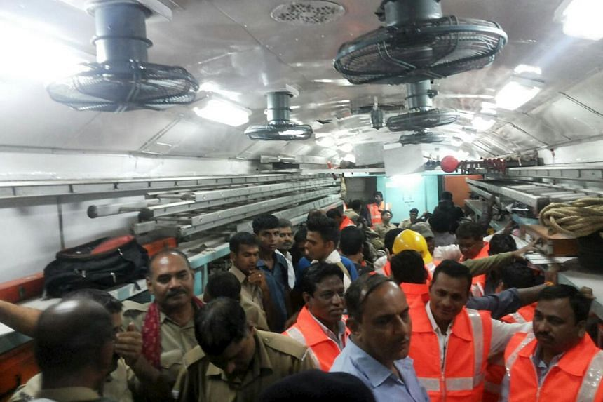 Officials and members of the rescue operation standing in a carriage of a derailed train near Harda, Madhya Pradesh in this handout provided by ANI.