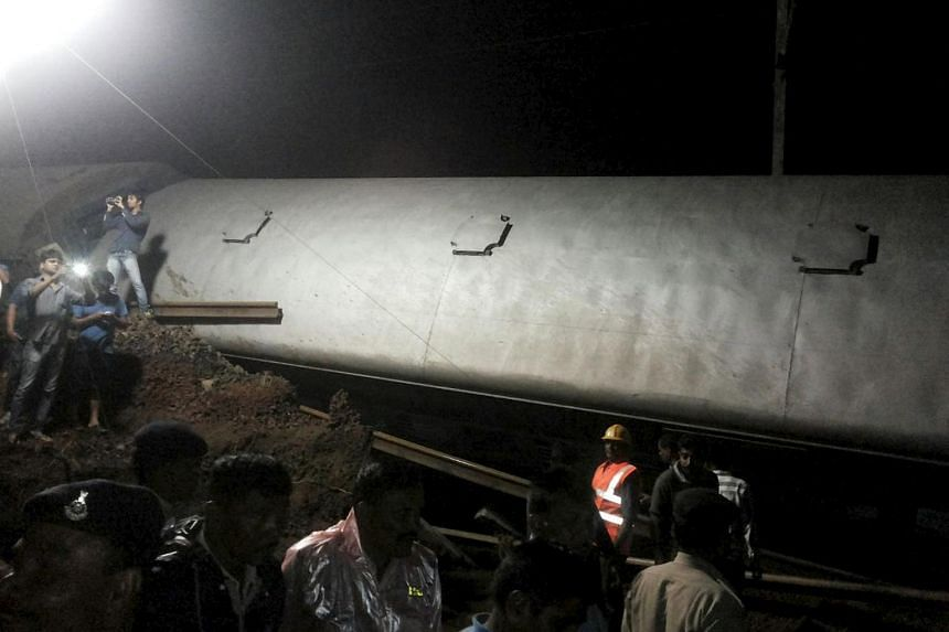 Police and members of the rescue operation standing at the site of a train derailment near Harda, Madhya Pradesh in this handout provided by ANI.