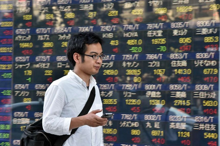 A man walking past a share prices board in Tokyo.