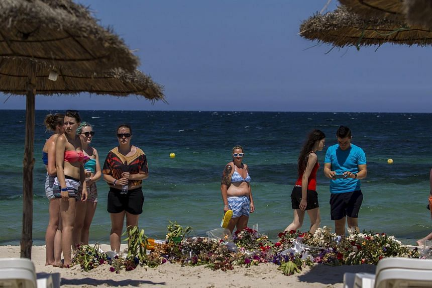 Tourists pay their respects in front of flowers laid out along a beachside in memory of the victims killed by a gunman at the Imperial Marhaba resort, in Sousse, Tunisia, on July 1, 2015.