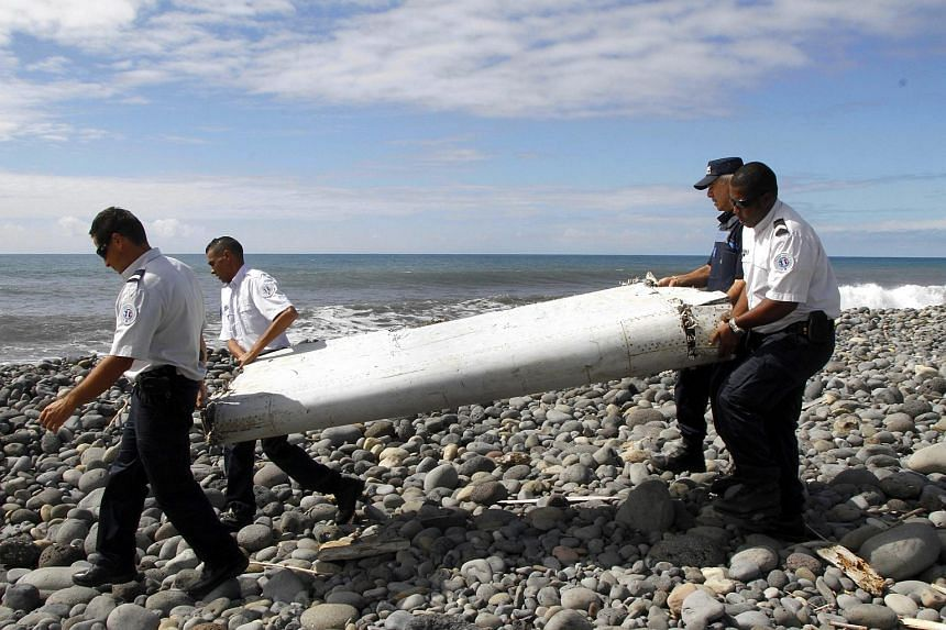 Officers carry pieces of debris from an unidentified aircraft apparently washed ashore in Saint-Andre de la Reunion, eastern La Reunion island, in France, on July 29, 2015.