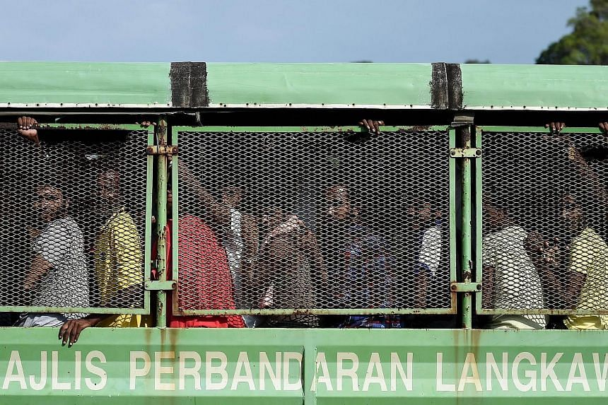 Bangladeshi and Rohingya migrants from Myanmar ride in a truck as they arrive at the naval base in Langkawi.