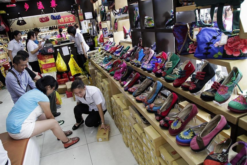 A sales staff attends to a customer trying shoes at a shopping district of Beijing, China on August 3, 2015.