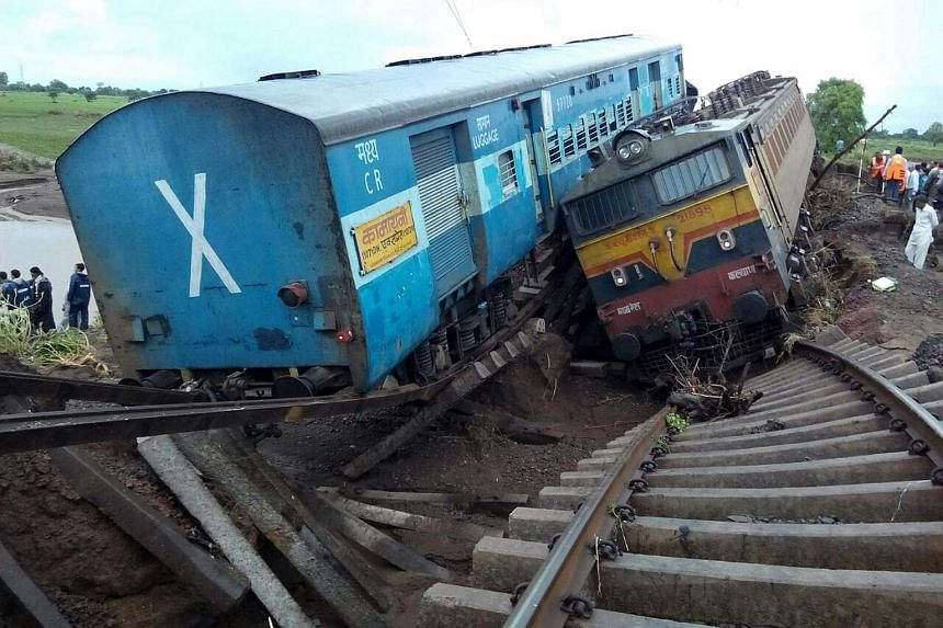 Two Indian passenger trains lay next to each other following a derailment after they were hit by flash floods on a bridge outside the town of Harda in Madhya Pradesh state.