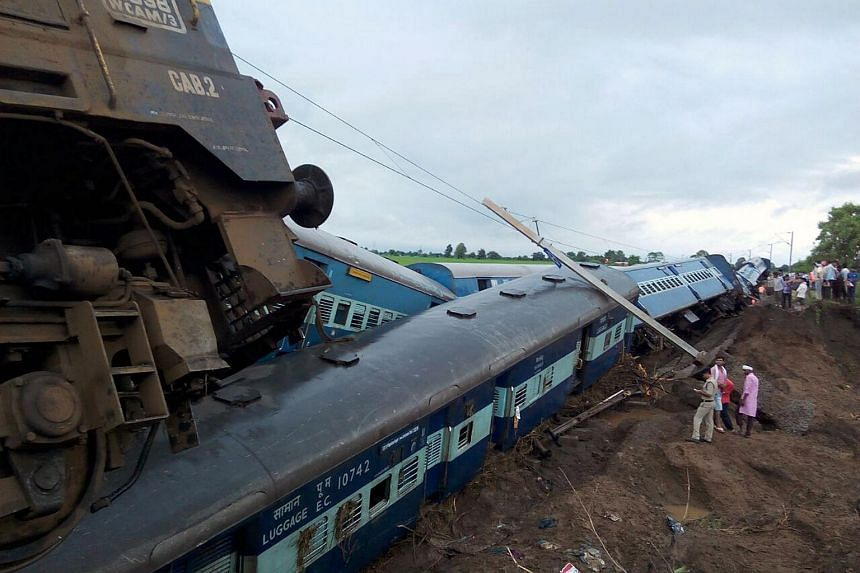 Indian officials stand next to two passenger trains on top of each other following a derailment after they were hit by flash floods on a bridge outside the town of Harda in Madhya Pradesh state.