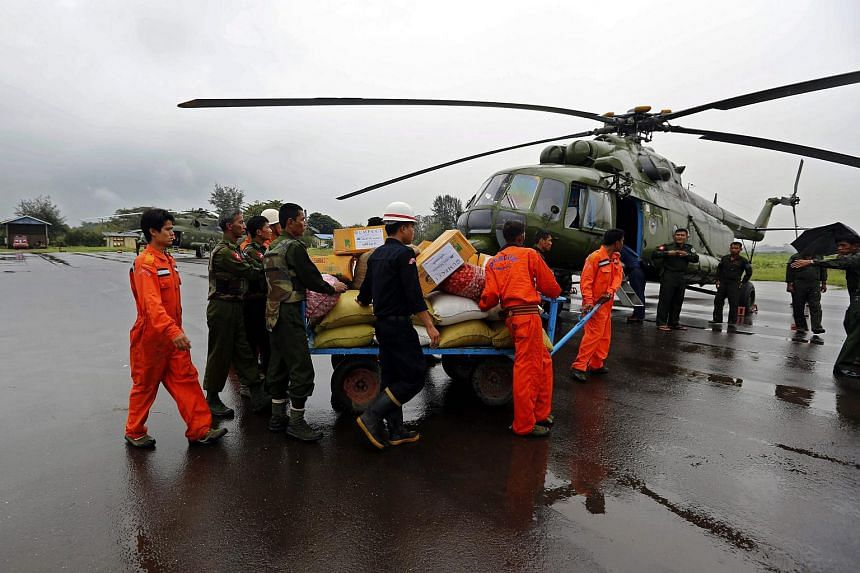 Soldiers and rescue workers carry aid near a military helicopter in Sittwe airport, Rakhine State, western Myanmar on August 4, 2015.