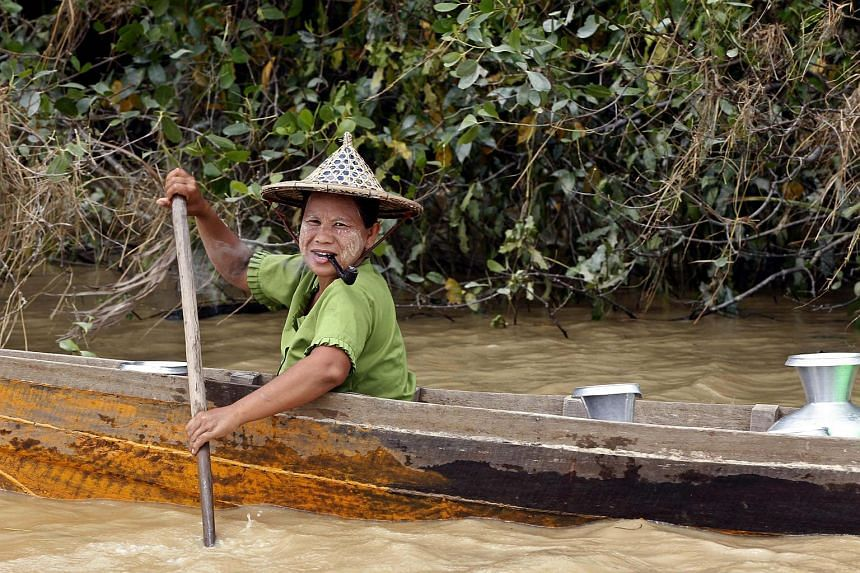 A woman looks out from a boat as she travels to get drinking water on a river in Mrauk-U, Rakhine State, western Myanmar, on Aug 4, 2015.