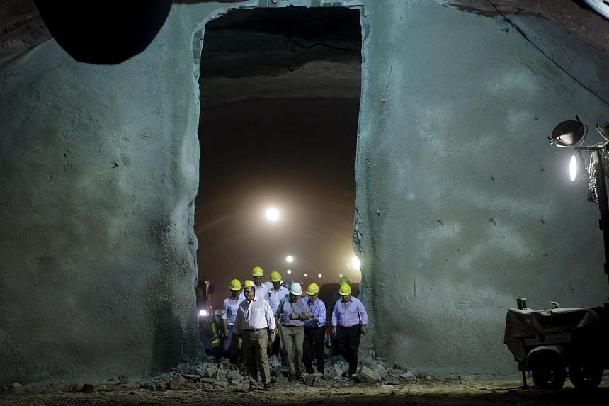 Rio de Janeiro's Governor Luiz Fernando Pezao (second, left), Rio de Janeiro's Mayor Eduardo Paes (centre) and Rio 2016 Olympic Games Organising Committee President Carlos Arthur Nuzman (second, right) walking through a tunnel which will connect the