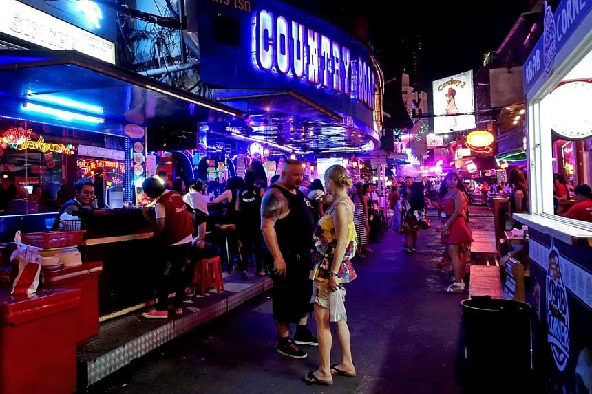 Revellers at Soi Cowboy, a lane filled with pubs popular with tourists in Bangkok. A new Thai government order threatens to revoke the licence of any establishment found selling alcohol to those under 20 years of age or selling beyond licensed hours.