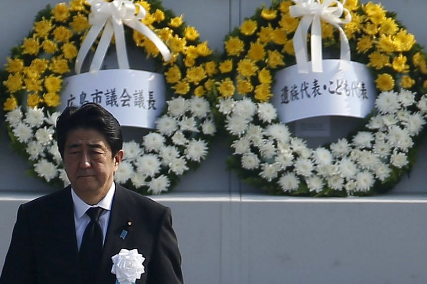 Japan's PM Shinzo Abe walking as he attends a ceremony at the Peace Memorial Park in Hiroshima on Aug 6, 2015, on the 70th anniversary of the world's first atomic bombing of the city.