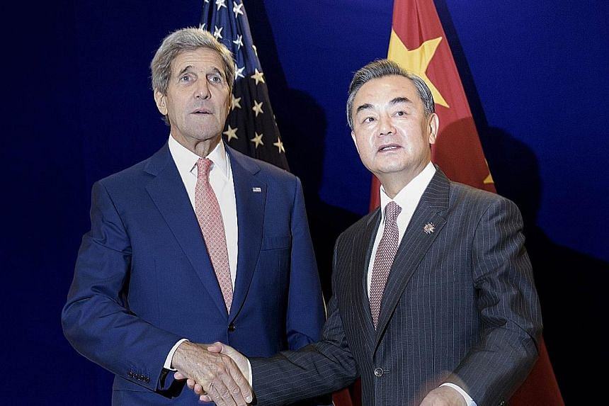 """US Secretary of State John Kerry and China's Foreign Minister Wang Yi meeting in Kuala Lumpur yesterday. Mr Wang put forward a three-point proposal for """"promoting peace and stability in the South China Sea"""" at a meeting with Asean foreign ministers."""