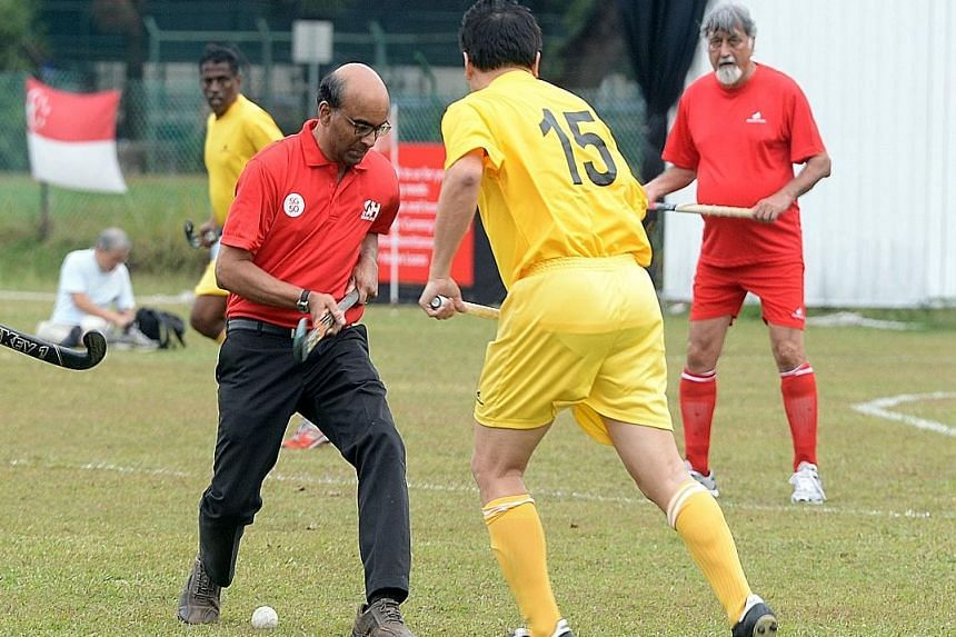 Deputy Prime Minister and Finance Minister Tharman Shanmugaratnam on the ball after bullying off the match between the Singapore ex-internationals and an Indian Association selection to celebrate the Republic's 50 years of independence. In the past 2