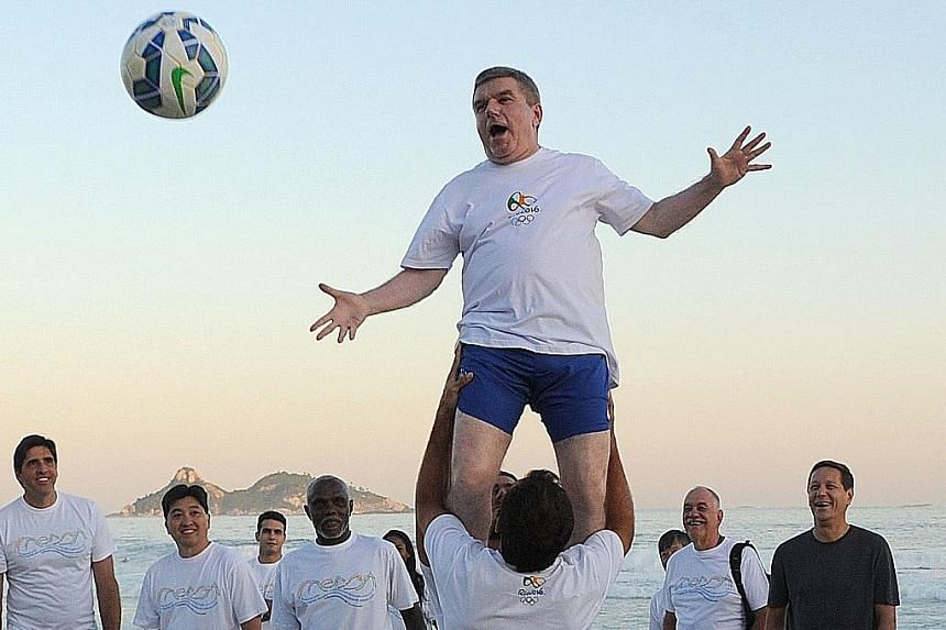 International Olympic Committee president Thomas Bach (top) takes part in an event at Barra da Tijuca Beach in Rio de Janeiro on Tuesday, one year before the start of the 2016 Olympic Games.