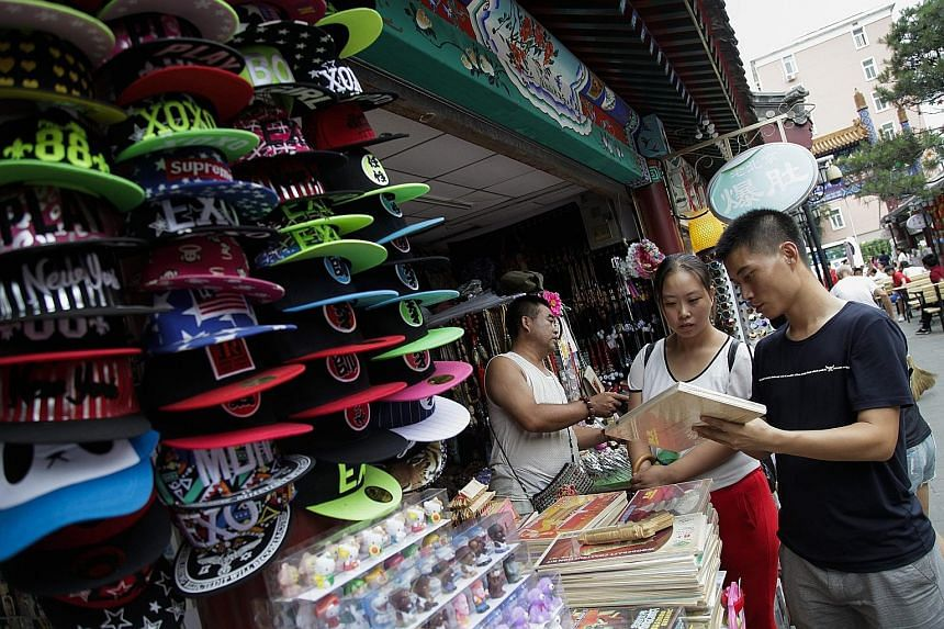 Customers at a shopping district in Beijing. China's economic slowdown is one of the factors contributing to the hammering of the 30 blue chips that make up the Straits Times Index. The stocks have dropped 7.6 per cent in the past 12 months.