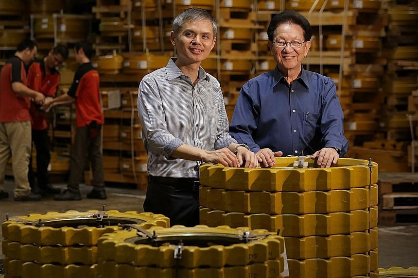 Kian Ann Engineering group managing director Loy Soo Chew (left), 48, and founder Low Han Cheong, 80, at their warehouse complex in Changi. Even though the company was bought by South Africa's Invicta Holdings in 2013, the latter wants local top mana