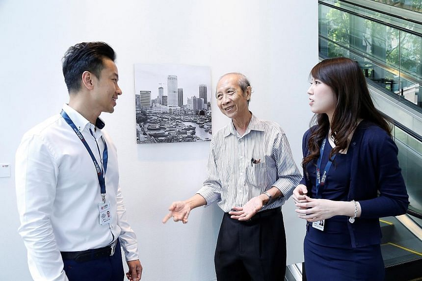 Pioneer generation artist Loke Hong Seng sharing his stories of Singapore in the 1960s with UOB employees at his exhibition at the UOB Art Gallery, as part of the bank's activities to celebrate SG50. The bank is giving about 7,500 employees ranked vi