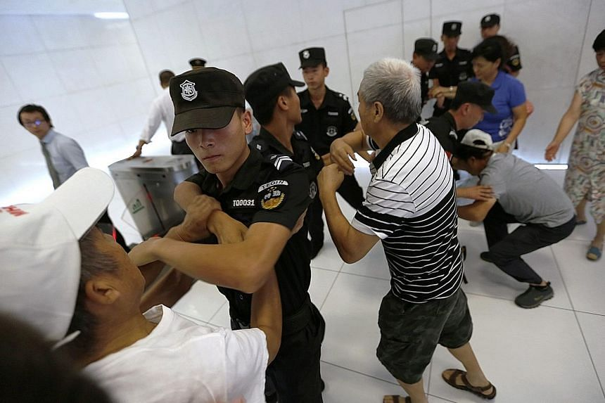 Relatives of Chinese passengers of the missing flight MH370 being stopped by police officers as they attempted to go up to the Malaysia Airlines office in Beijing yesterday.