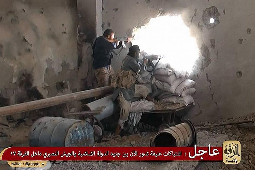 An image made available last year allegedly shows ISIS members firing at positions of pro-regime Syrian troops in rebel-held Raqa city.