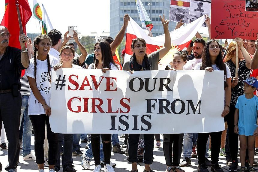 Protesters with banners and placards at a pro-Yazidi rally on the Place des Nations in front of the UN's European headquarters in Geneva, Switzerland, on Monday. ISIS has made a particular practice of enslaving those it has conquered who are not Sunni Mus