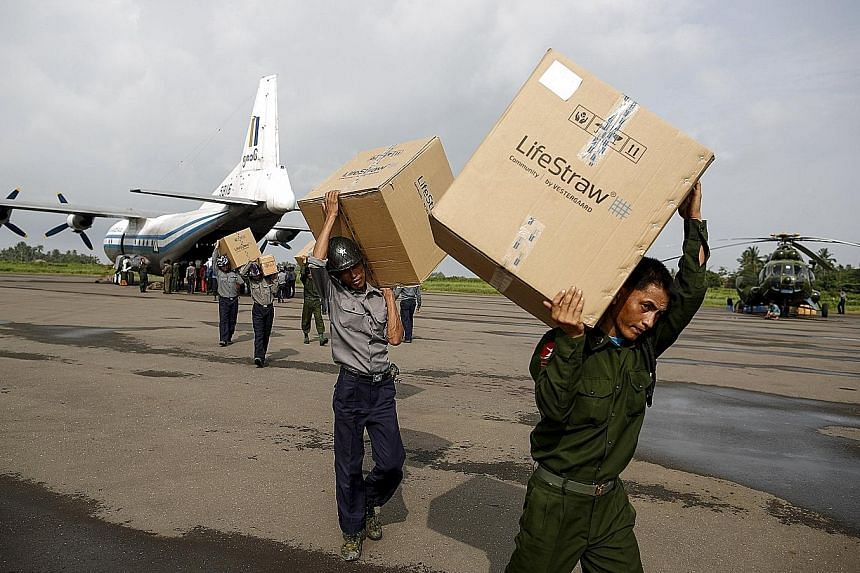 Soldiers and rescue workers unloading aid from a plane in Sittwe airport, Rakhine state, yesterday. The full nationwide picture remains unclear, with communications across the vast but poor country severed by the floods.