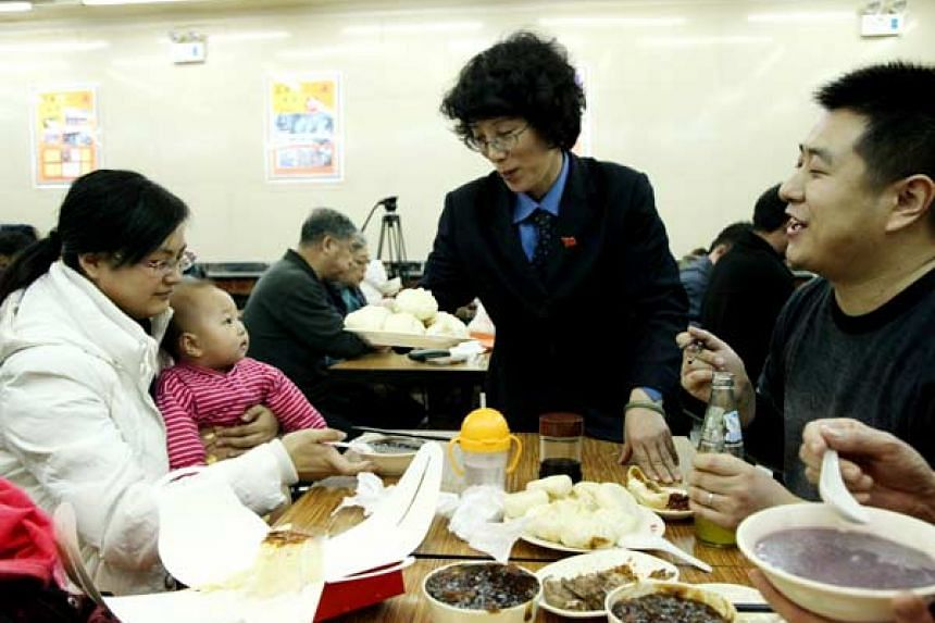 The manager of Qing Feng Steamed Dumpling Shop in Beijing serving customers.
