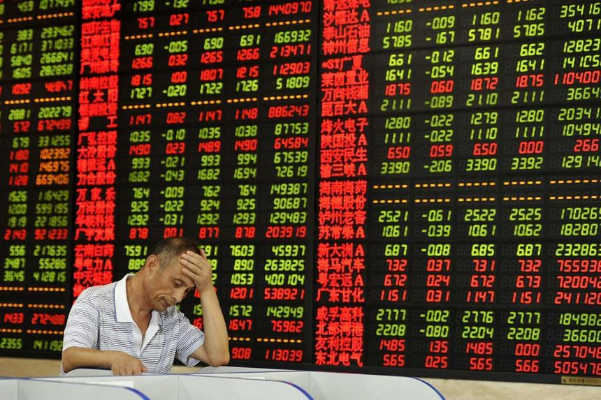 An man looking at a computer screen in front of an electronic board showing stock information in China.