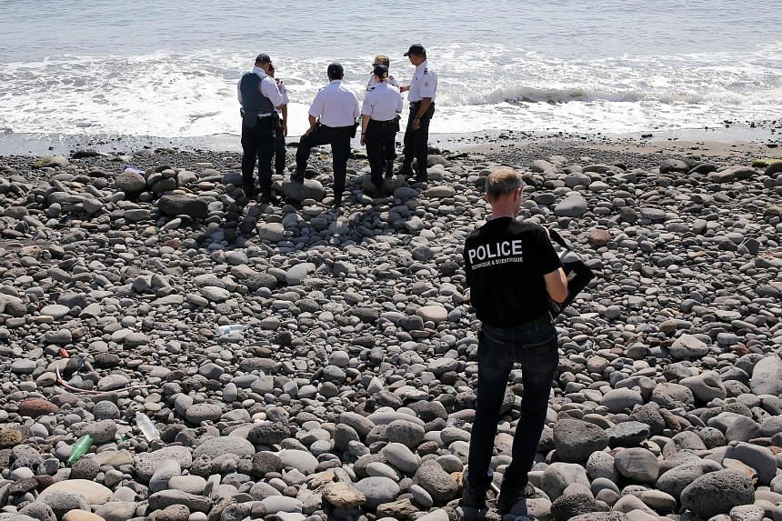 Police officers inspect metallic debris found on a beach in Saint-Denis on the French island of Reunion in the Indian Ocean on Aug 2, 2015.