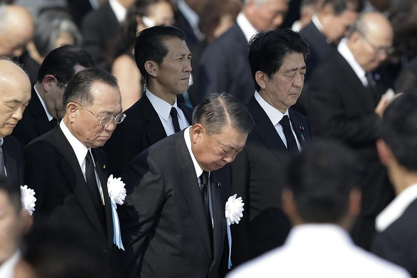Japanese Prime Minister Shinzo Abe (right) observes a moment of silence for victims killed by the atomic bombing in Hiroshima on Aug 6, 2015.