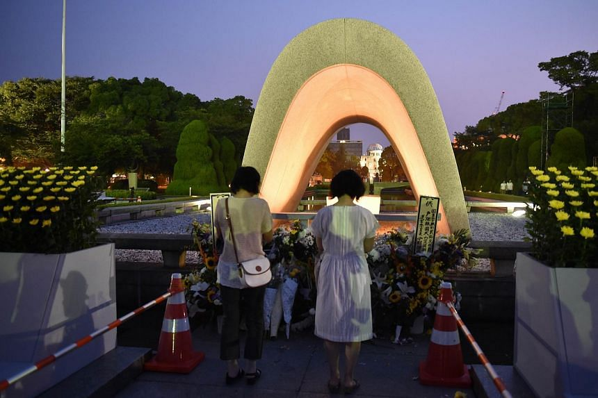 Women pray for the victims of the 1945 atomic bombing, at the Peace Memorial Park in Hiroshima on Aug 6, 2015.