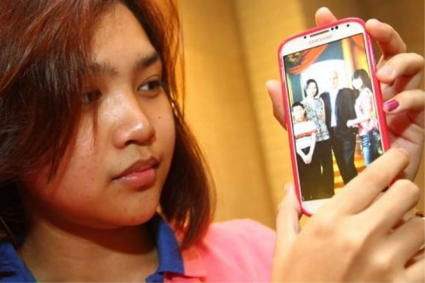 Ms Maira Elizabeth Nari, the eldest child of MH370 chief steward Andrew Nari, showing a family photo on her handphone.
